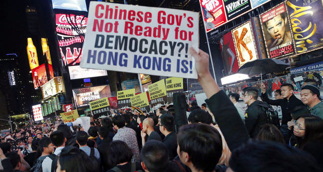 Protesters show their solidarity with Hong Kong protesters during a rally Wednesday, Oct. 1, 2014, in Times Square in New York. They demanded a stop to violent police repression of democracy activists currently occupying central areas of Hong Kong. (AP Photo/Kathy Willens)